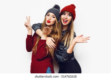 Happy smiling pretty friends hugging and showing peace hand sign on white background. Cute cheerful women in stylish   knitted  hat and sweaters having fun, laughing, hugging.