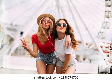 happy smiling pretty girls having fun.stylishly dressed in short denim shorts and bright t-shirts, sunglasses