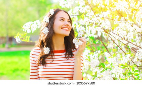 Happy smiling pretty young woman with spring flowers at garden