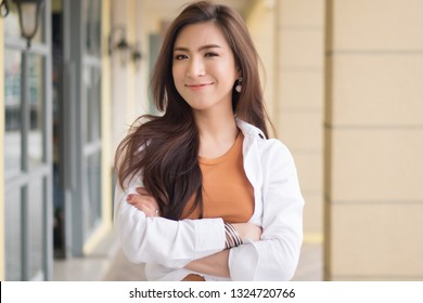 happy smiling proud asian woman; portrait of smart casual girl, positive happy smiling asian woman on urban background; asian chinese young adult woman model