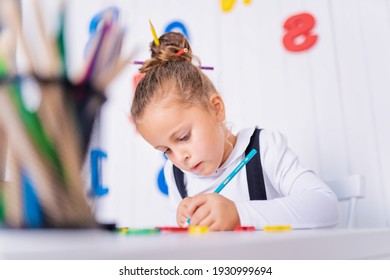 Happy smiling pupil at the desk. Child in the class room with pencils, books. Kid girl from primary school. first day of fall. Back to school.