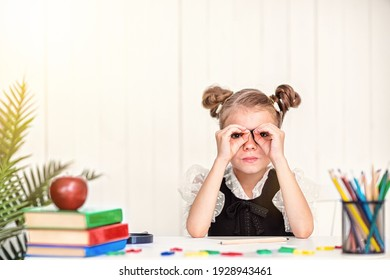 Happy smiling pupil at the desk. Girl in the class room with pencils, books. Kid girl from primary school. first day of fall. Back to school.