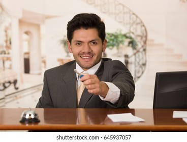 Happy smiling receptionist in hotel giving key to guest, hotel background