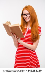 Happy smiling redhead girl in glasses and red sptriped dress reading a book isolated on white background