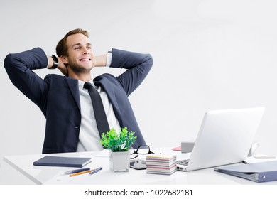 Happy smiling relaxing or dreaming businessman with hands behind head, in black suit working with laptop computer at office. Success in business, job and education concept.