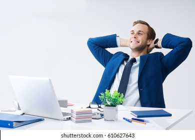 Happy smiling relaxing or dreaming businessman with hands behind head, in blue suit working with laptop computer at office. Success in business, job and education concept.