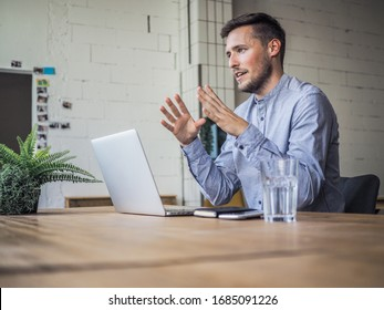 happy smiling remote online working man having his hand up with laptop and notebook in casual outfit with sitting in an coworking or home office at a work desk explaining something