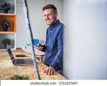 feliz sonriente trabajador en línea tecleando y mirando a la pantalla de un portátil con teléfono móvil, portátil y planta en ropa informal parado frente a un escritorio en una oficina de trabajo
