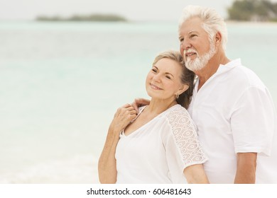 Happy smiling retired senior Caucasian couple living a healthy outdoor island lifestyle on Caribbean beach