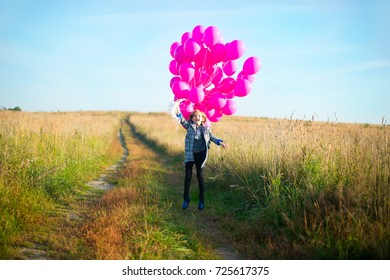 Happy smiling school girl walking in autumn field with many colorful balloons in hand ready to celebrate her birthday