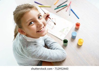 Happy smiling schoolgirl is drawing. Photo of a cute little girl doing homework. Education concept