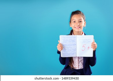 Happy smiling schoolgirl in uniform holding and showing notebook with excellent results of test or exam on blue background