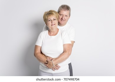 Happy smiling senior couple standing together on white background