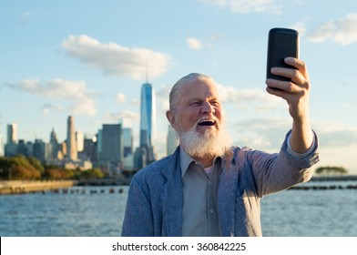 Happy smiling senior man taking a selfie in a beautiful day at river side. Senior healthy man enjoying is retirement. Casual joyful grandfather taking a selfie with the skyscrapers in the background.