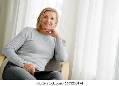 Happy, smiling senior woman 60-65 years old with blonde hair sitting in armchair and surfing internet on tablet computer at home. Old lady with tablet pc at home. Concept of lifestyle, technology.