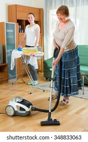 Happy smiling senior woman and adult girl cleaning together at home