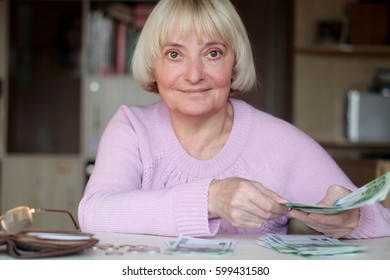 Happy smiling senior woman, an elderly pensioner holding euro banknotes, wallet with money at the table, concept of financial security in old age, indoor portrait
