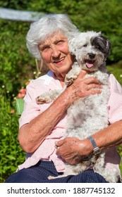 Happy Smiling Senior Woman Hugging her Havanese Dog Outdoor in the Nature