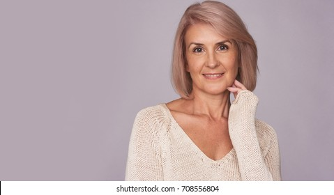 Happy smiling senior woman isolated on grey background. Anti aging concept