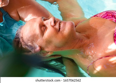 Happy smiling senior woman receiving water spa head massage with toothy smile and closed eyes in swimming pool relaxing feeling fresh