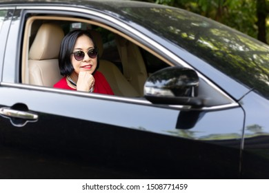 Happy smiling senior woman sitting in a car.