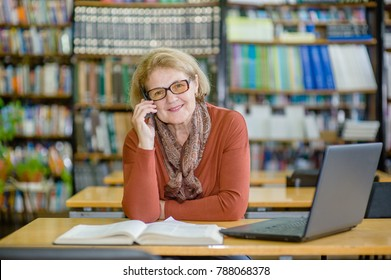 Happy smiling senior woman using mobile phone in library