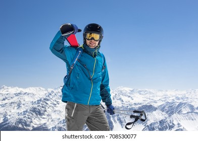 Happy smiling skier during active winter holidays. Man in winter clothing walking in snow and carrying ski on shoulder. Sporty man skiing with copy space of blue sky and snowy mountain.