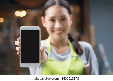 happy smiling small business owner, entrepreneur showing smartphone blank screen