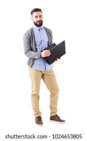 Happy smiling smart casual man holding laptop and looking at camera. Full body length portrait isolated on white studio background.