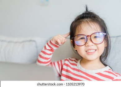 Happy smiling smart and nerd little asian girl in glasses and pointing finger at brain holding laptop in sofa living room.Child with school kindergarten.Child development and Education concept.