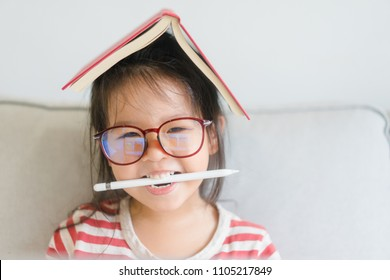 Happy smiling smart and nerd little asian girl in glasses and red book.Child with school kindergarten.Child development Education and home school kid concept.