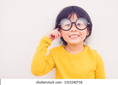 Happy smiling smart and nerd little asian girl in glasses and pointing finger at brain and going to school for the first time.Child with school kindergarten.Child development and Education concept.
