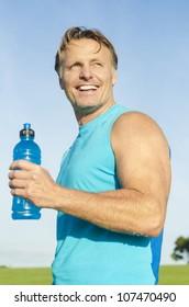 happy smiling sportsman holding a blue water bottle.