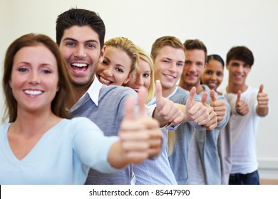 Happy smiling students in a row with their thumbs up