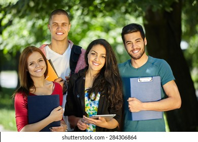 Happy smiling Students with tablet, computer at Park