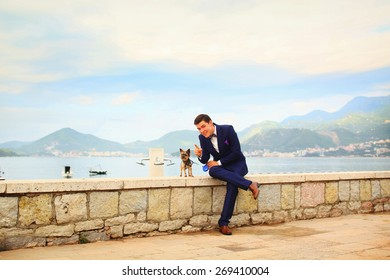 happy smiling stylish rich groom sitting on a pier with a Yorkshire Terrier Montenegro