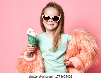 Happy smiling stylish rich kid girl in faux fur coat and sunglasses holds big tasty ice cream with candies in waffles cone on pastel pink background