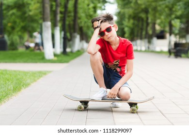 Happy smiling stylish teen boy with a skateboard in outdoors. Concept lifestyle and sportive life.