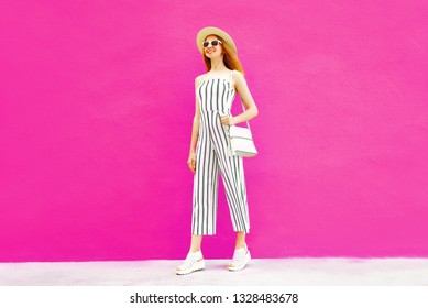 Happy smiling stylish woman in summer round straw hat, white striped jumpsuit on colorful pink wall background