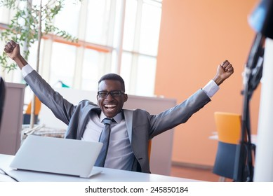 Happy smiling successful African American businessman  in a suit in a modern bright office indoors