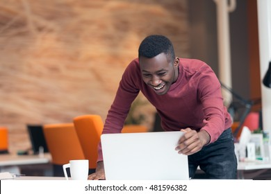Happy smiling successful African American businessman in a modern startup office indoors
