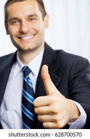 Happy smiling successful businessman with thumbs up gesture, at office. Focus on hand. Success in business and teamwork concept.