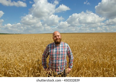 Happy smiling successful caucasian thirty years old farmer standing proud in front of his wheat fields