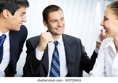 Happy smiling successful gesturing businessman with document and colleagues at office. Teamwork, partnership, meeting, brainstorming, conculting and business success concept.