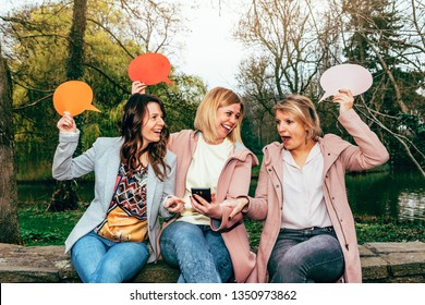 happy, smiling and surprised females friends are at the park communicating with a mobile phone and holding a speech bubble