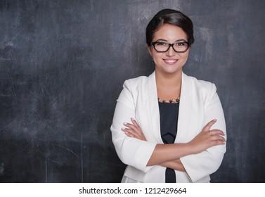 Happy smiling teacher on blackboard background
