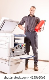 happy smiling technician man near printer copier with red fire e