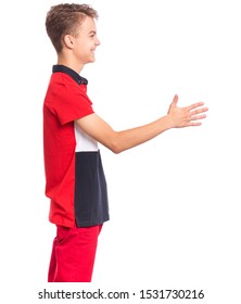 Happy smiling teen boy giving hand for handshake - side view, isolated on white background. Teenager stretching hand in greeting gesture - profile.