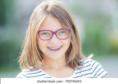 Happy smiling teen girl with dental braces and glasses.