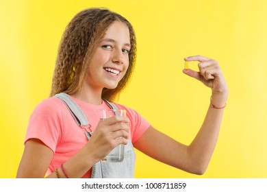 Happy smiling teen girl taking pill with cod liver oil omega-3 and holding glass of fresh water with yellow backgrounde. Diet, nutrition, healthy eating, lifestyle. Vitamin D, E, A fish oil capsules.